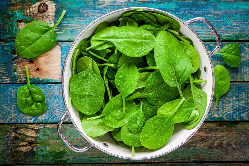 39448993 - raw fresh spinach with drops in a colander on a rustic wooden table