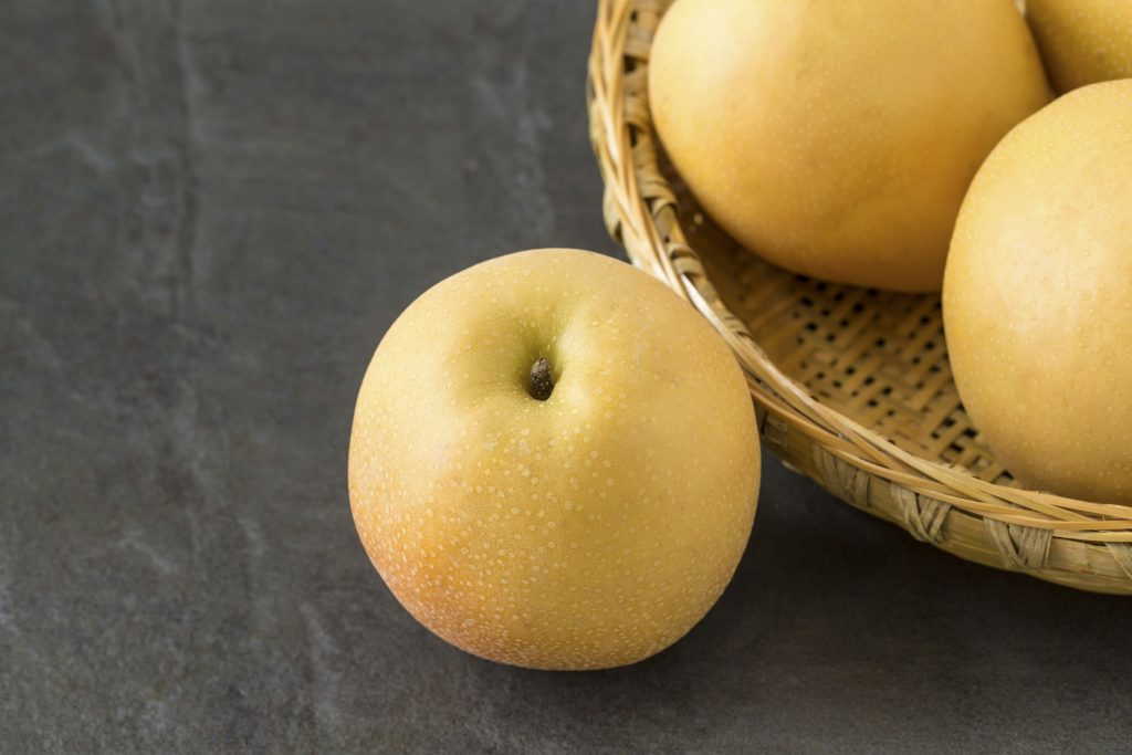 54108158 - asian pears with a bamboo basket on the slate background